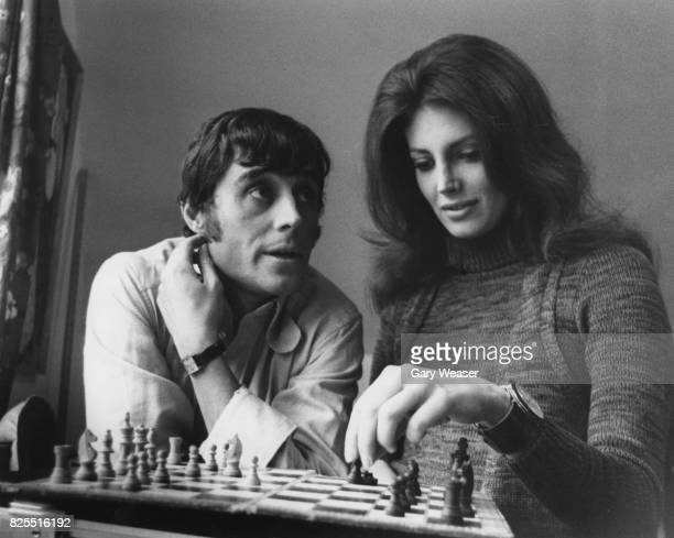 American actress Gayle Hunnicutt playing chess with actor Ian McShane her costar in the film 'Freelance' between takes at a house in Muswell Hill...