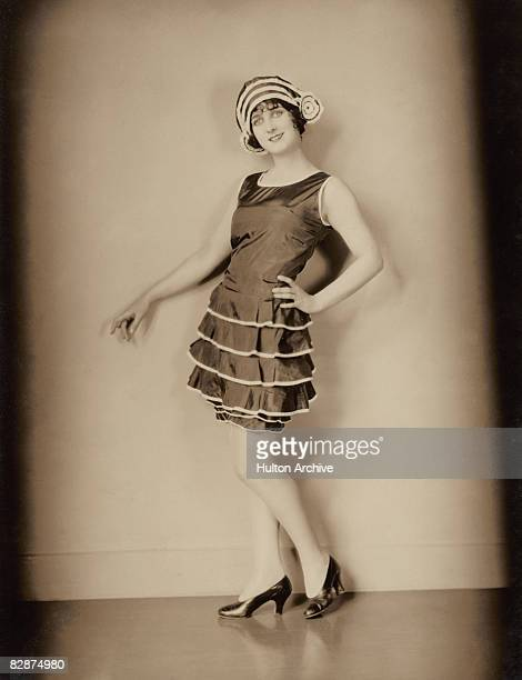 American actress Gertrude Olmstead wearing a black silk taffeta bathing suit with ruffles edged with white satin ribbon circa 1925