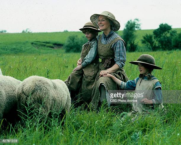American actress Glen Close sits in a field with child actors Christopher Bell and Lexi Randall in a scene from the television movie 'Sarah Plain and...