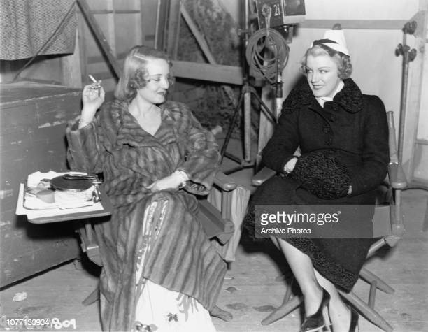 American actress Glenda Farrell visits Bette Davis on the set of the Warner Bros film 'Kid Galahad' 1937 Davis stars in the movie