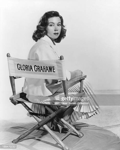 American actress Gloria Grahame sitting in a director's chair bearing her name circa 1955