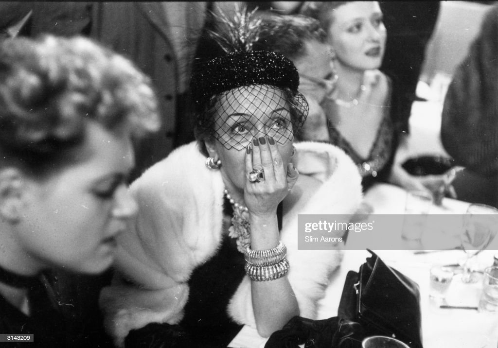 American actress, Gloria Swanson, anxiously awaits the results of the Best Actress award at a cafe on West 52nd Street, New York. On her left is her fellow nominee and the eventual winner, Judy Holliday.