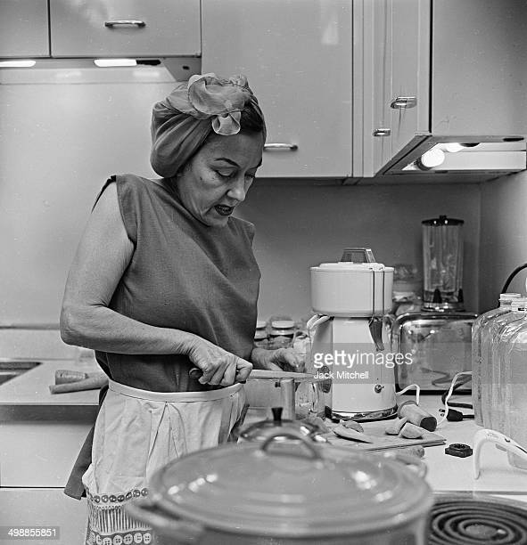 American actress Gloria Swanson prepares a meal in her kitchen New York New York 1962