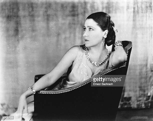 American actress Gloria Swanson seated in a studded armchair