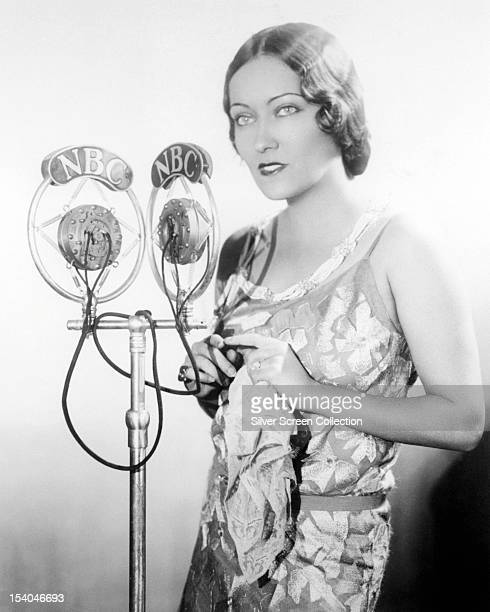 American actress Gloria Swanson standing at a pair of NBC microphones circa 1925