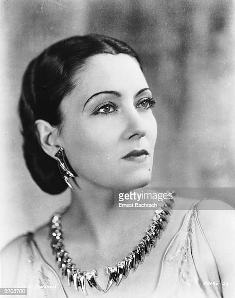 American actress Gloria Swanson wearing a necklace and matching earrings shaped like sharks' teeth