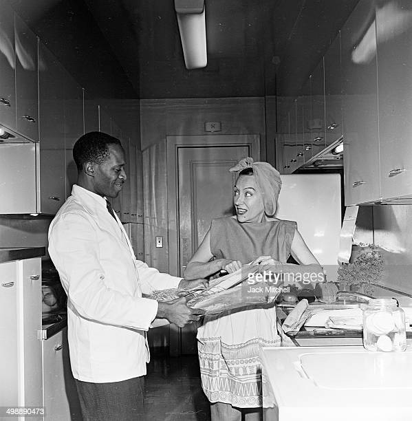American actress Gloria Swanson with her butler in the kitchen of her home New York New York 1962