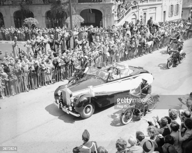 American actress Grace Kelly and Prince Rainier III of Monaco drive through the streets in their Rolls Royce car after their wedding ceremony at...