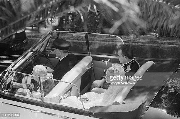 American actress Grace Kelly and Rainier III, Prince of Monaco (1923 – 2005 are driven through the streets of Monte Carlo in a convertible car...