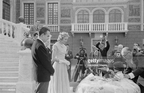 American actress Grace Kelly and Rainier III Prince of Monaco about to receive the gift of a white dove on the day of their civil wedding ceremony at...