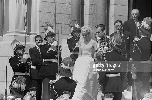 American actress Grace Kelly and Rainier III Prince of Monaco walk down the steps of Saint Nicholas Cathedral flanked by a military guard after their...