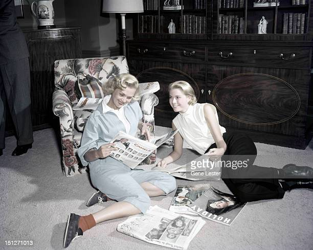American actress Grace Kelly reading magazines with a friend 1954