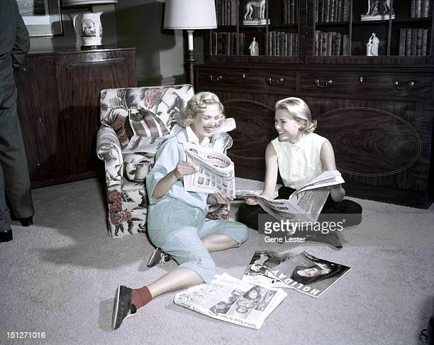 American actress Grace Kelly reading magazines with a friend, 1954.