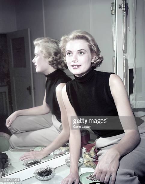 American actress Grace Kelly wearing a black sleeveless top, 1954.