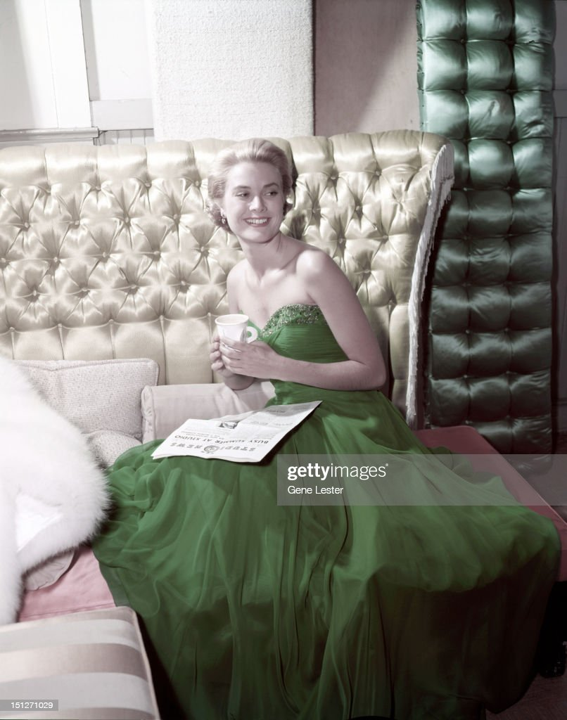 American actress Grace Kelly (1929 - 1982) wearing a green dress for St Patrick's Day, 1954. She is reading a copy of MGM's Studio News.