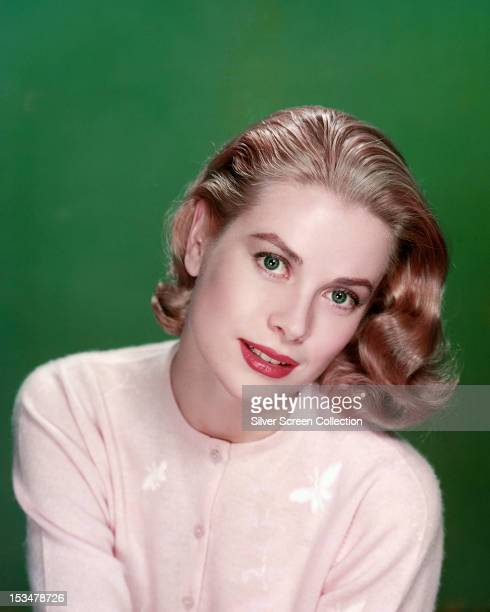American actress Grace Kelly wearing a pink cardigan, circa 1955.