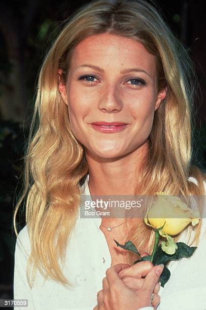 American actress Gwyneth Paltrow smiling and holding a yellow rose