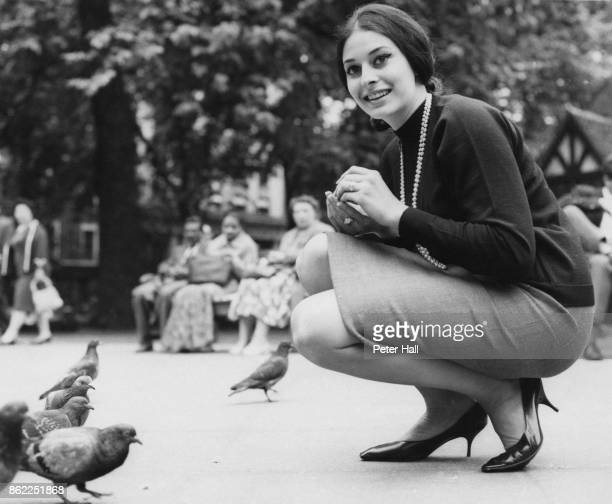 American actress Ina Balin feeds the pigeons in Soho Square during a holiday in London 12th June 1961