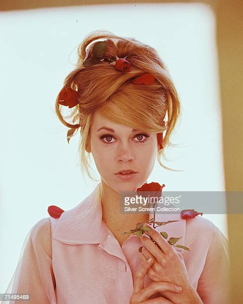 American actress Jane Fonda adorned with red roses circa 1965