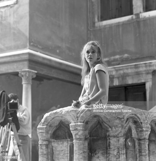 American actress Jane Fonda caressing a cat and sitting on a well in the 'Remer' square Venice 1967