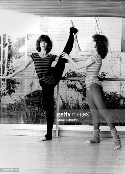 American actress Jane Fonda exercises during a photo shoot for 'Jane Fonda's Workout Book,' Los Angeles, California, 1981. The woman on the right is...