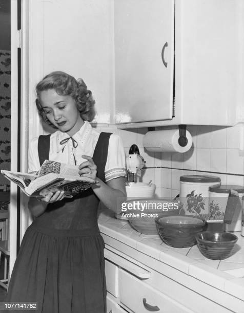 American actress Jane Powell leafs through the 'Modern Encyclopedia of Cooking' for a good recipe circa 1950