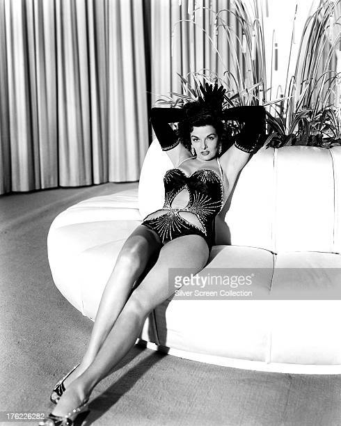 American actress Jane Russell reclining on a sofa, in evening gloves and a cut-away, one-piece swimsuit, in a promotional portrait for the 3D musical...