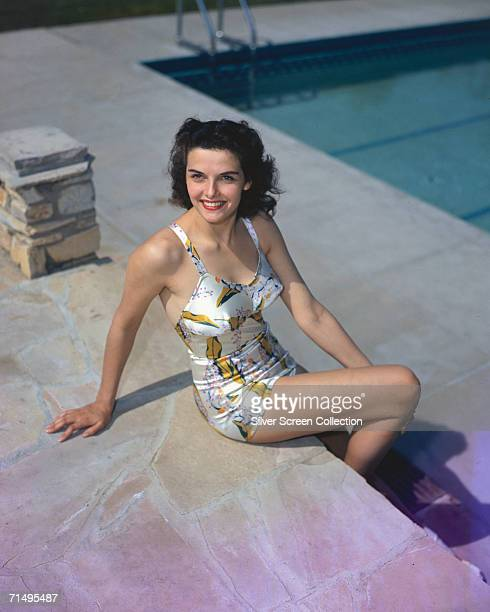 American actress Jane Russell sits by the side of a swimming pool, circa 1950.