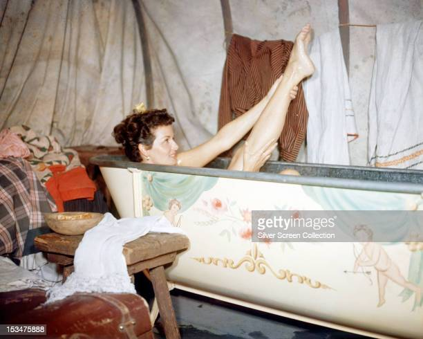 American actress Jane Russell , taking a bath, as Nella Turner in 'The Tall Men', directed by Raoul Walsh, 1955.