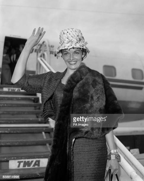American actress Jane Russell waves to the crowds and press after landing at London Airport from Hollywood sporting a hat featuring falling leaves...