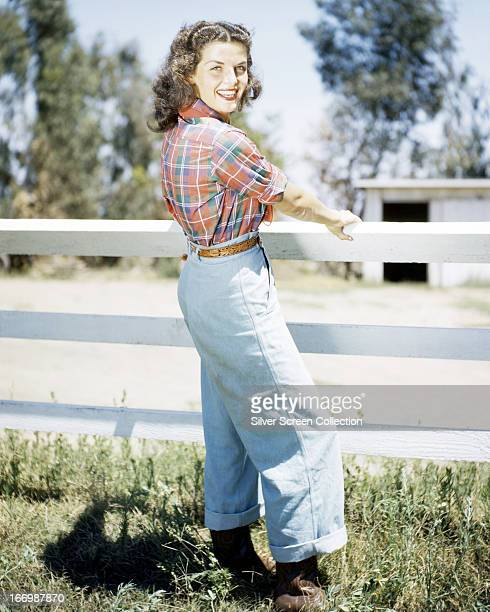 American actress Jane Russell wearing denim jeans and a plaid shirt circa 1950