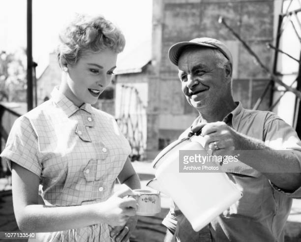 American actress Janet Leigh accepts a cup of coffee from maintenance man Mickey Robinson on the set of the MGM film 'A Steak For Connie' aka...
