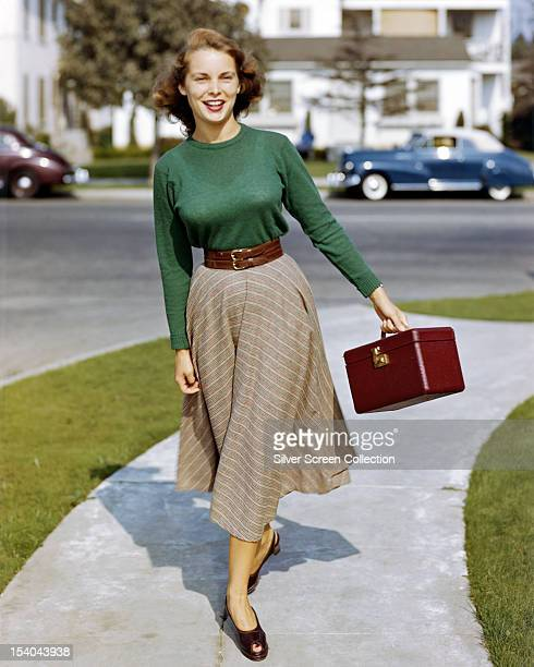 American actress Janet Leigh carrying a makeup case on a suburban street USA circa 1950