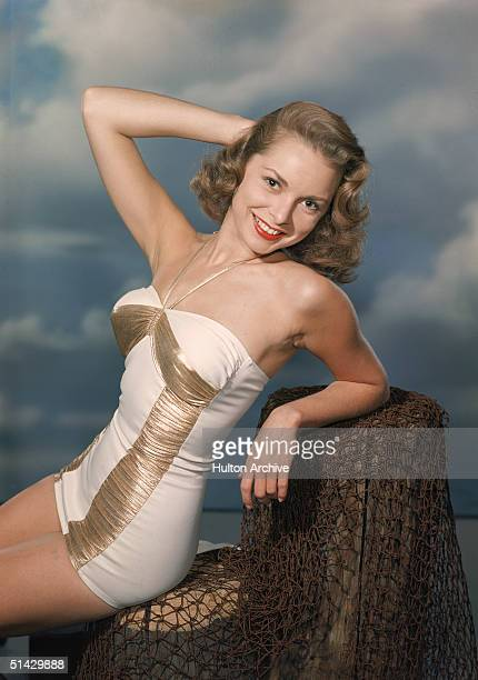American actress Janet Leigh sits and poses on a fake pier in a white and gold bathing suit late 1940s