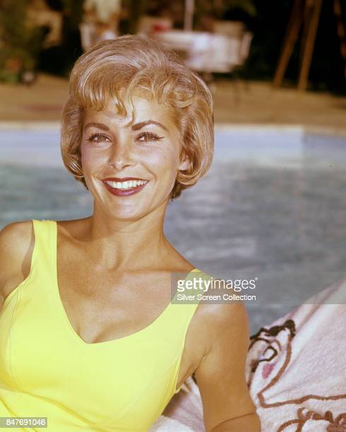 American actress Janet Leigh smiles smiles from a lounger near a swimming pool circa 1955