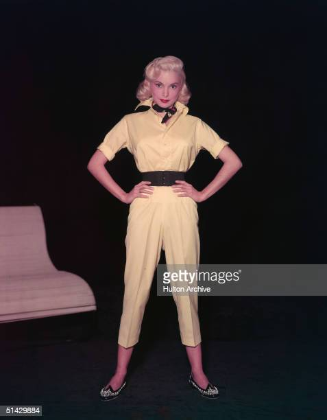 American actress Janet Leigh stands with arms akimbo in a yellow shortlegged jumpsuit with a wide belt beaded shoes and a neckerchief 1950s
