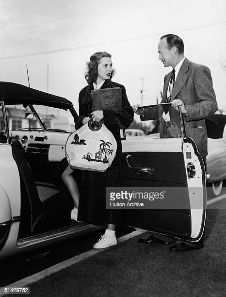 American actress Janet Leigh talks to her father Fred Morrison as she gets into a car and holds a large embroidered handbag and a bound album reading...