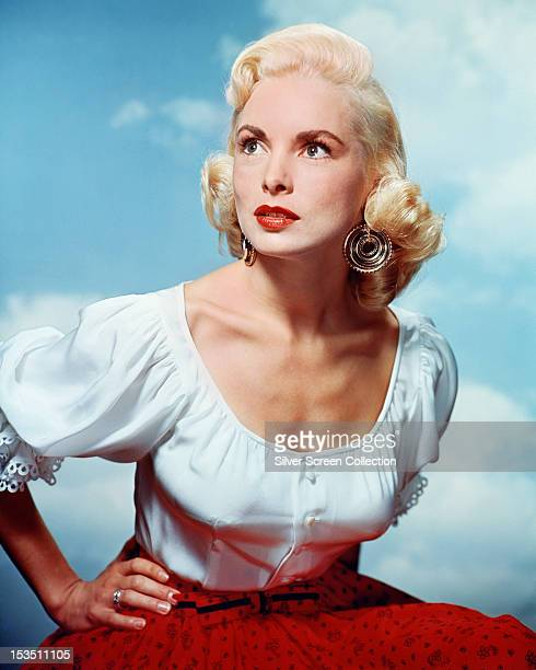 American actress Janet Leigh wearing earrings, a low-cut white top and a red skirt, circa 1955.