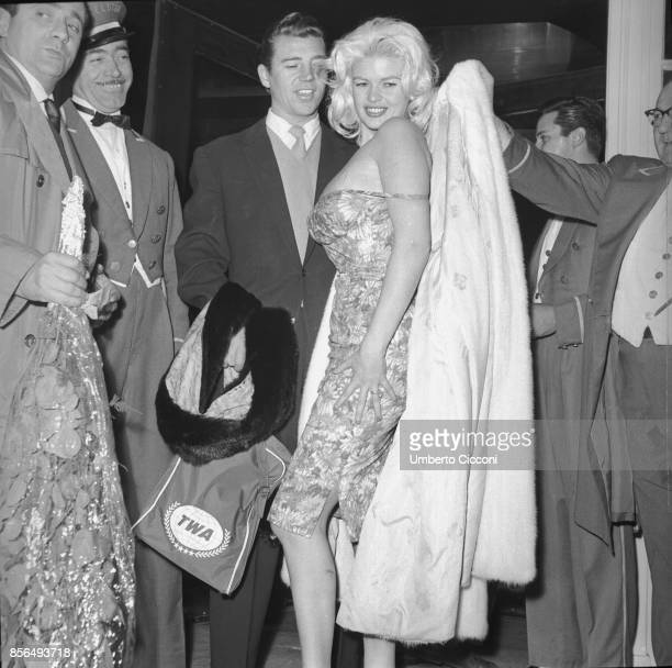 American actress Jayne Mansfield and actor Mickey Hargitay in a restaurant in Via Veneto Rome 1959 A man is giving to Jayne Mansfield a jacket before...