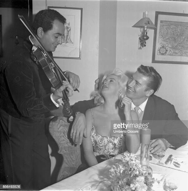 American actress Jayne Mansfield and actor Mickey Hargitay listening to a violinist in a restaurant in Via Veneto Rome 1959