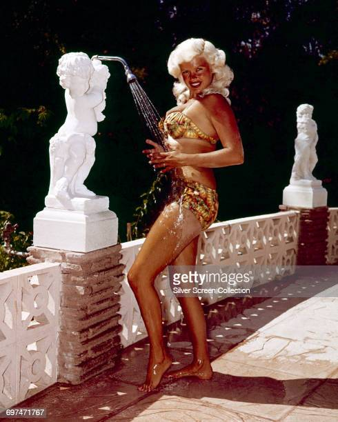 American actress Jayne Mansfield cools off under an ornate outdoor shower, circa 1965.