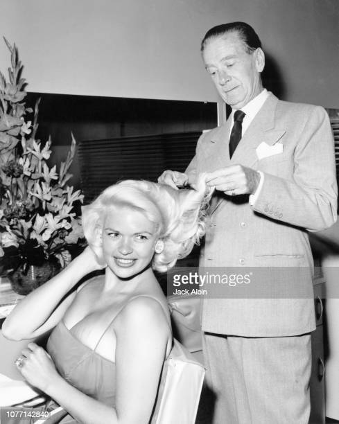 American actress Jayne Mansfield has her hair combed by actor and singer Clifton Webb as a joke at the Cinema Hairstylists salon on the Sunset Street...