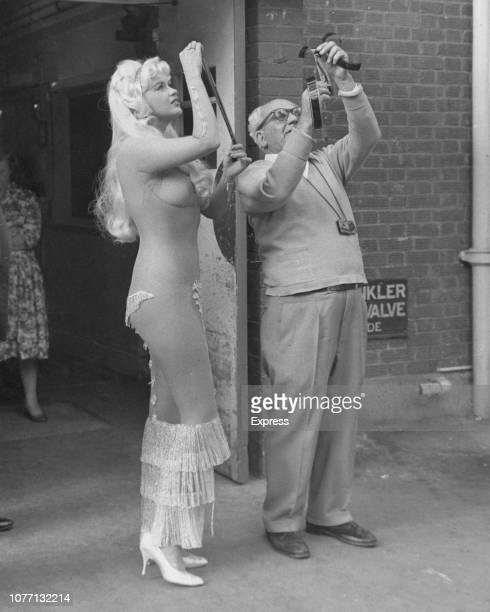 American actress Jayne Mansfield in costume for the film 'Too Hot To Handle' aka 'Playgirl After Dark' 16th September 1959 She is examining film...