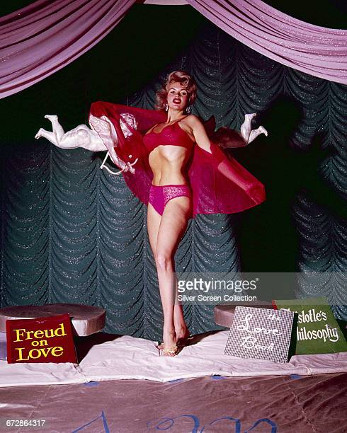 American actress Jayne Mansfield leaves no doubt as to her status as a sex symbol by posing with two cherubs and copies of 'Freud on Love' 'The Love...