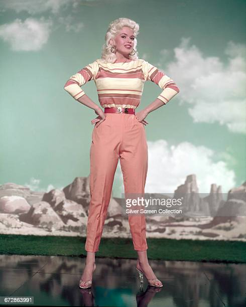 American actress Jayne Mansfield poses against a painted desert backdrop in peachcoloured trousers and a striped top circa 1960