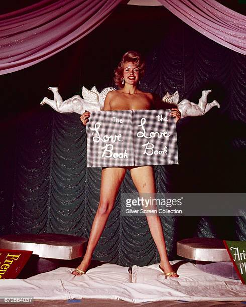 American actress Jayne Mansfield posing apparently nude behind a copy of 'The Love Book' while two plaster cherubs hover behind her circa 1955