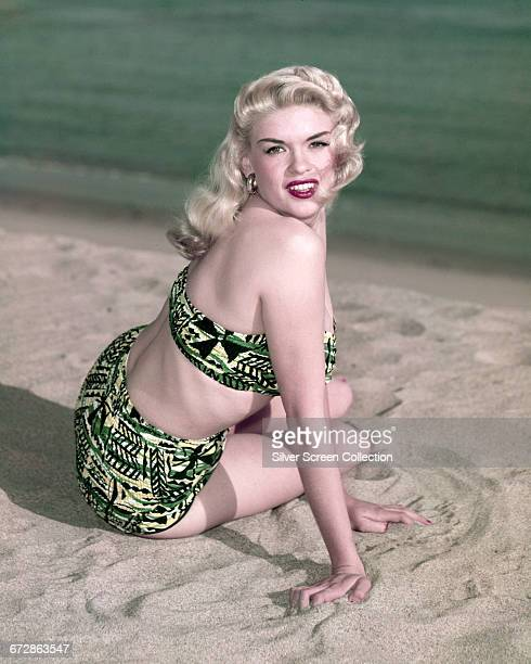 American actress Jayne Mansfield posing on the beach in a bikini circa 1955