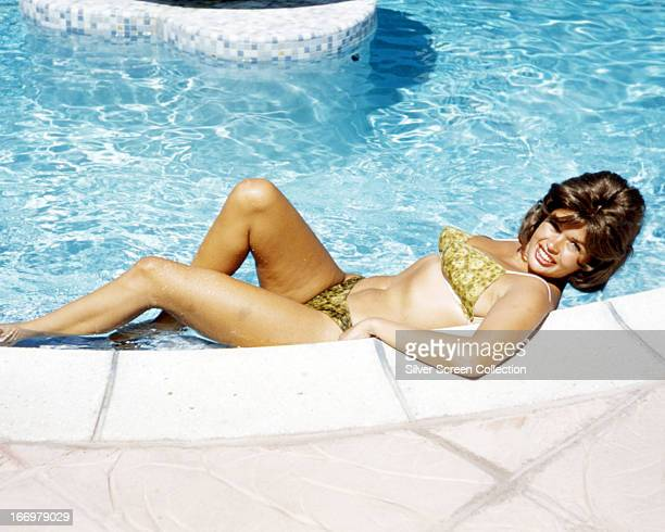 American actress Jayne Mansfield reclining by a swimming pool in a bikini circa 1965