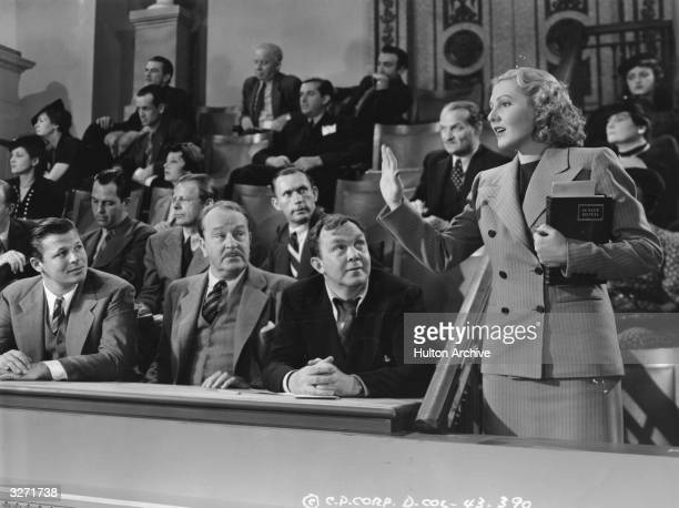 American actress Jean Arthur formerly Gladys Greene swearing in at court in the presence of actors Thomas Mitchell and Jack Carson in a scene from...