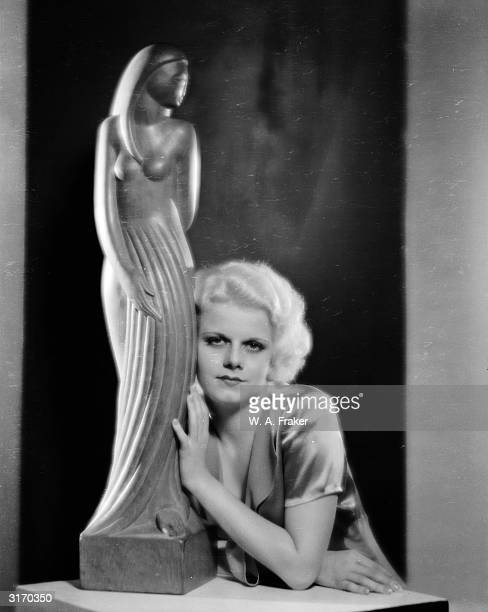 American actress Jean Harlow leaning against a statuette.